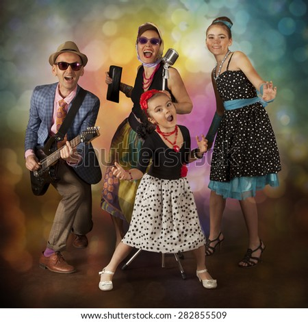 Rockabilly family band playing music and singing on a black background with glowing lights - stock photo