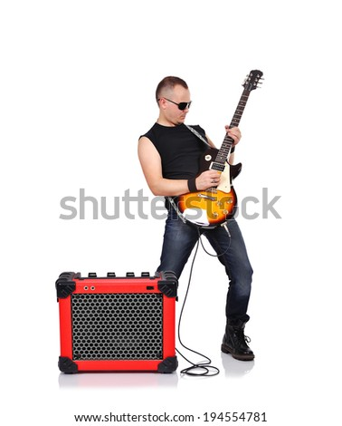 rocker playing on electrical guitar and guitar combo - stock photo