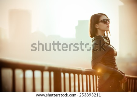 Rocker,punk woman.Young rock woman in black leather jacket casual standing with city background at sunset.Rock bad girl.Sexy attractive woman with punk rock fashion styling.Image toned and noise added - stock photo