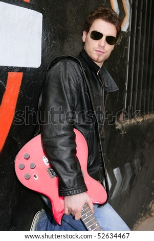 rocker rock star man on black graffiti holding red electric guitar leather jacket