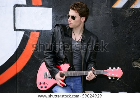 rocker rock star man on black graffiti holding red electric guitar leather jacket - stock photo