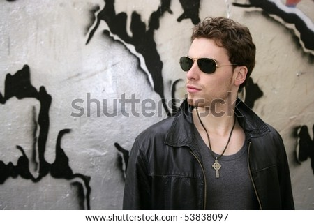 rocker rock star young man sunglasses on silver wall city outdoor - stock photo