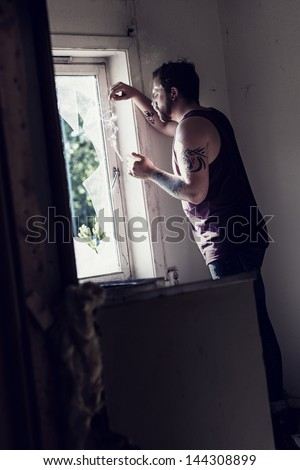 Rocker standing by a broken window and smoking cigarettes and thinking.