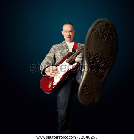 rocker with electric guitar putting foot in camera - stock photo
