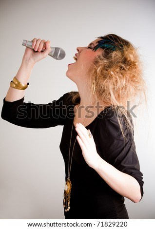 Rocker woman with messy hairdo singing with a microphone - stock photo