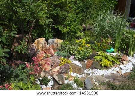 Rockery with flowers in the garden - stock photo