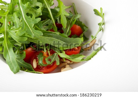 Rocket salad with cherry tomatoes and pine nuts served on white plate, closeup