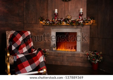 Rocking chair in the living room with decorated modern flaming fireplace