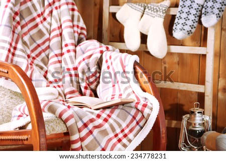 Rocking chair with plaid and book near wooden wall - stock photo