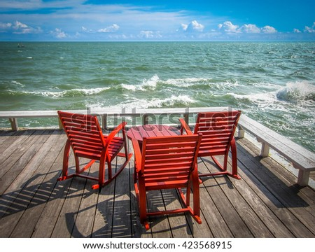 Rocking chairs on the wooden deck at beach front