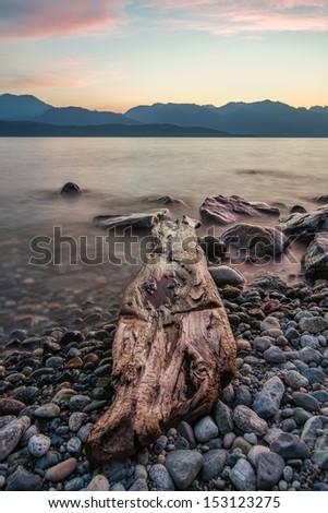 Rocks along lake shore with log. - stock photo