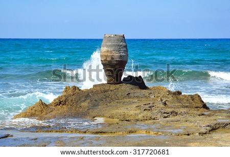 Rocks and decorative vase on the Aegean coast in Malia, Crete, Greece. - stock photo