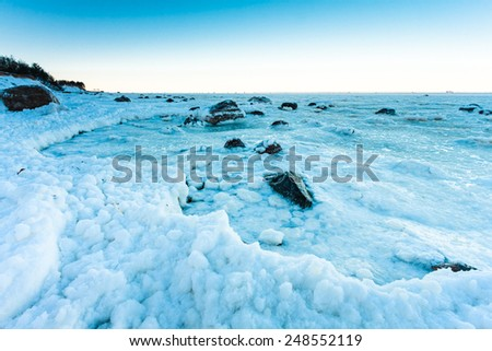 Rocks and pebbles covered with ice after snow storm on Gulf of Finland, Russia