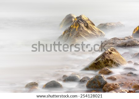 Rocks at Osmington Reflecting Sunset Colours - stock photo