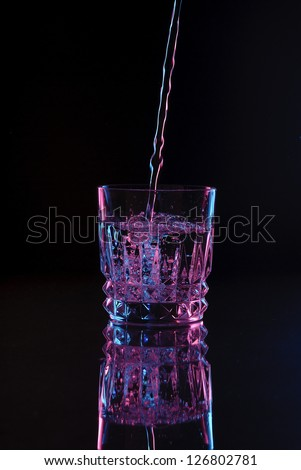 Rocks Glass Tumbler Cocktail Glass Filling up Pouring Water or Liquid, Dark Field, Color Gels Lighting - stock photo