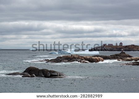 Rocks, icebergs and lighthouse in rural Newfoundland, Canada. - stock photo