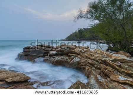 rocks in a blue ocean under cloudy sky in a bad weather. Long exposure photography - stock photo