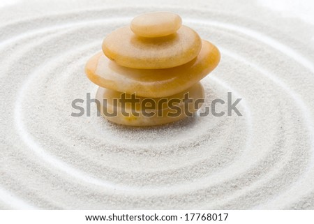 rocks in equilibrium with sand forming circles background - stock photo