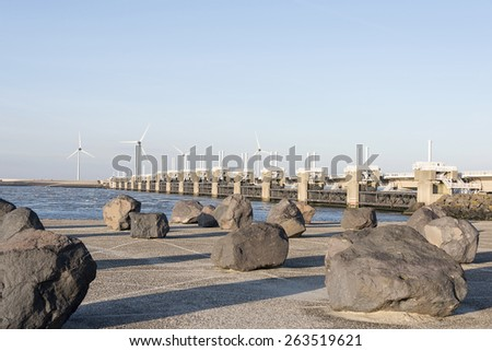 rocks in front of the deltaworks in holland at the Oosterschelde river to protect holland form high sea level, this is near the dutch museum neeltje jans - stock photo