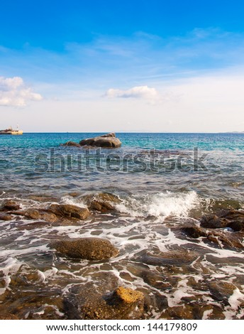 Rocks in the blue sea, illuminated by the sun. Background.