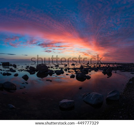 Rocks in the sea with sunset sky. - stock photo