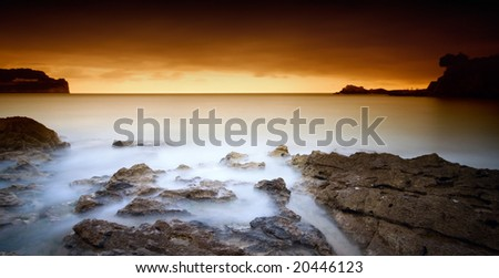 rocks in the water covered of foam and fog under a red sunset - stock photo