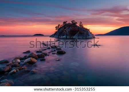 Rocks leading to Whyte island at high tide, Whytecliff park in West Vancouver, British Columbia at Dusk - stock photo