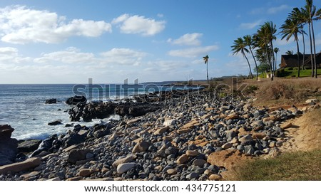 Rocks line Kepuhi Beach with Coconut trees along the shore on the island of Molokai in the state of Hawaii - stock photo