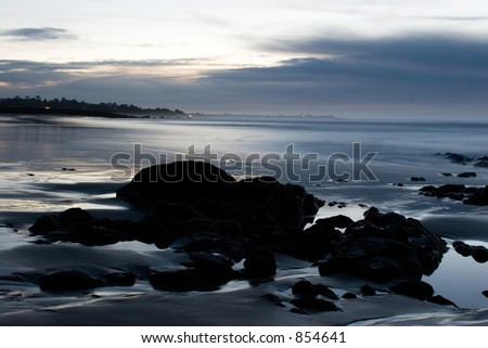 rocks on a beach at sunset - stock photo