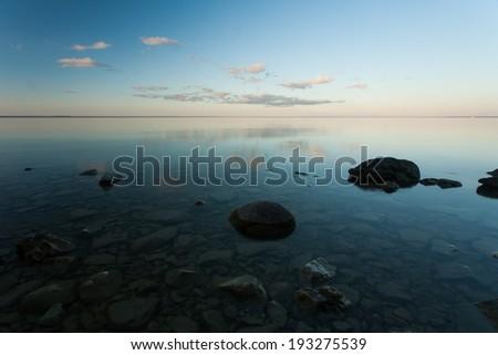 Rocks on a beach at sunset.  Mackinac Island, MI, USA. - stock photo