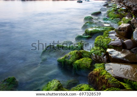 Rocks on black sea with waves at sunset and green moss.
