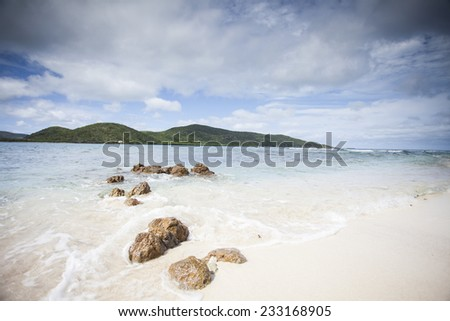 Rocks On The Caribbean Sea Shore With Clouds, Blue Skies, Clear Blue Water, And White Sand Beaches - stock photo