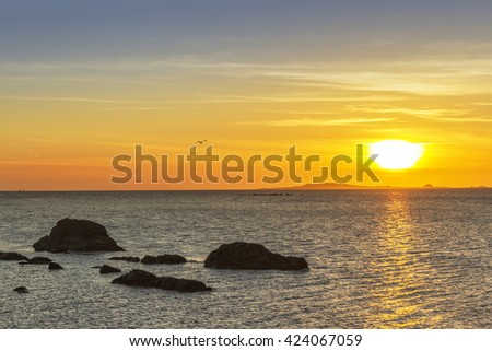 Rocks on the sea and sunset over Salvora and Noro islands in Arousa estuary