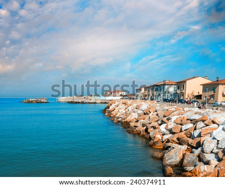 Rocks over the oceans. Beautiful seascape with village homes at sunset. - stock photo