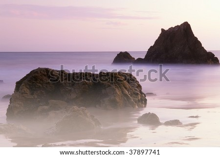 Rocks sit in the surf at sunset at a California Beach in Malibu