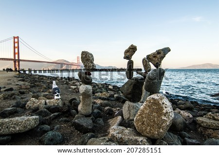 Rocks stacked by hand in front of scenic Golden Gate Bridge in San Francisco Bay - stock photo