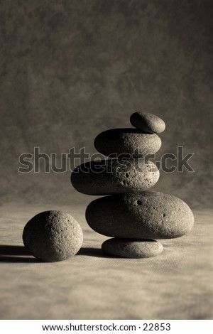 Rocks stacked one on top of another to create an precarious leaning tower of Zen. room above and below for copy. - stock photo