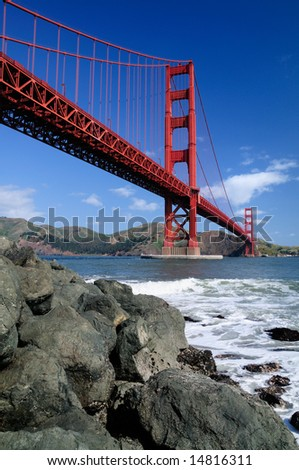 Rocks under Golden Gate Bridge. Shot from Fort Point, San Francisco. - stock photo