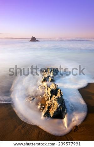 rocks with silky water in Sopelana beach - stock photo