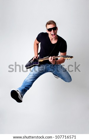 Rockstar men jumping with guitar while playing