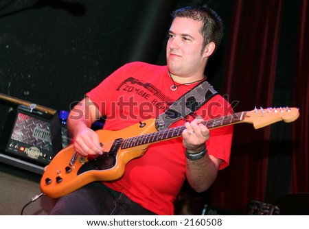 Rockstar playing guitar on stage - stock photo