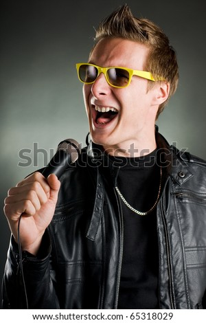 rockstar sings with yellow sunglasses and leather jacket - stock photo