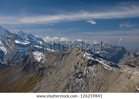 Rocky and snowy mountain range with deep blue sky and wispy clouds - stock photo