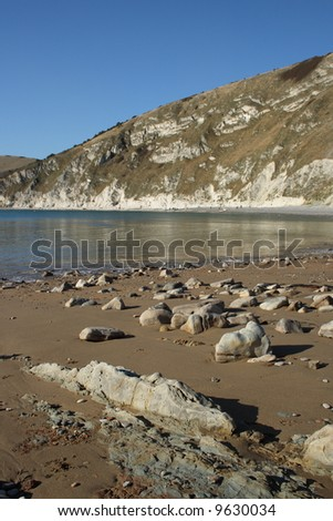 Rocky beach and distant chalk cliffs in Dorset England. - stock photo