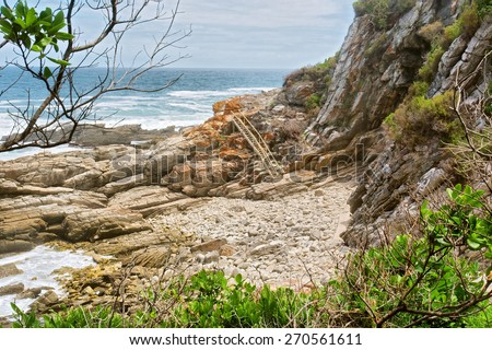 Rocky beach and ladder. Shot on the Otter trail in the Tsitsikamma National Park, Garden Route area, Western Cape, South Africa.  - stock photo