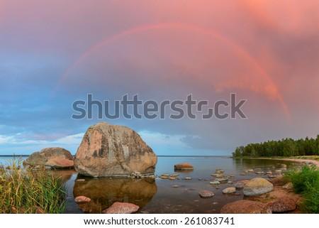 Rocky beach and rainbow in the Northern Coastline of Estonia. - stock photo