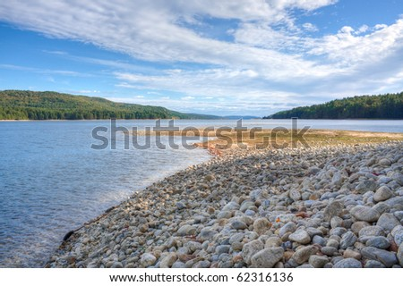 rocky beach at reservoir with beautiful view - stock photo