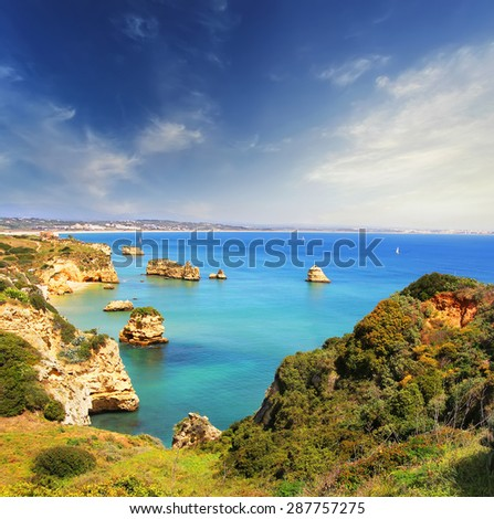 Rocky beach at sunset, Lagos, Portugal. Counter light. Travel and business background - stock photo