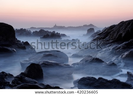 Rocky beach from the north of Portugal at dusk. Long exposure. - stock photo