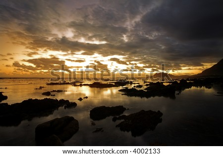 Rocky Beach of Betty Bay in Western Cape, South Africa at sunset on a cloudy day - stock photo